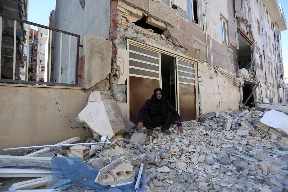 Homem é fotografado sentado sobre destroços, nesta segunda-feira (13), após tremor que atingiu a província iraniana de Kermanshah. (Foto: Tasnim News Agency/ Reuters)