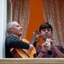 Foto: (Italianos cantam em Roma nesta sexta-feira (13) durante a quarentena imposta por causa do novo coronavírus na Itália / Guglielmo Mangiapane/Reuters)