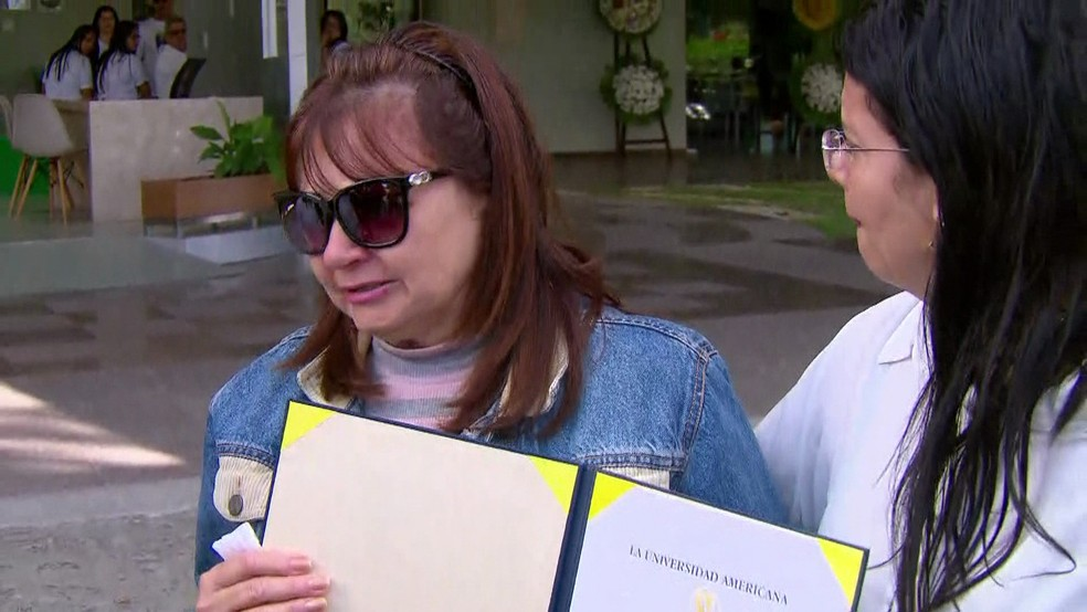 Mãe de Rayneia Lima, a aposentada Maria José da Costa levou o diploma da filha para o velório, no Cemitério Morada da Paz, em Paulista, no Grande Recife, nesta sexta-feira (3) (Foto: Reprodução/TV Globo)