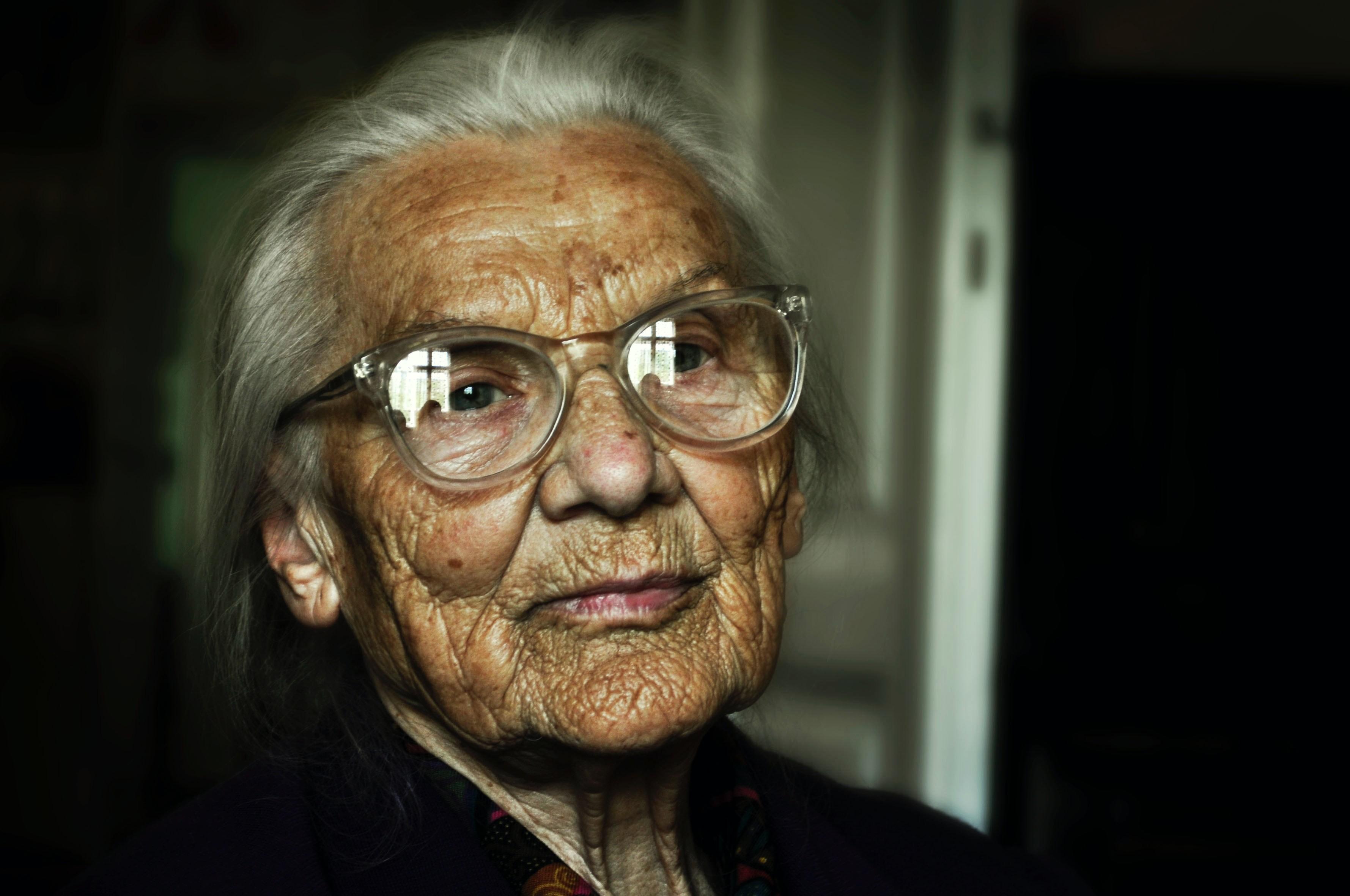 Idosos com Alzheimer são mais vulneráveis à infecção por Covid-19, aponta estudo. Acima: Idosa em um cômodo pouco iluminado olha para o horizonte (Foto: mali desha/Unsplash)