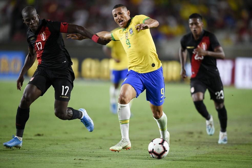 Richarlison no duelo com Advíncula no segundo tempo: Pombo foi quem mais finalizou nas duas partidas, com nove tentativas — Foto: AFP