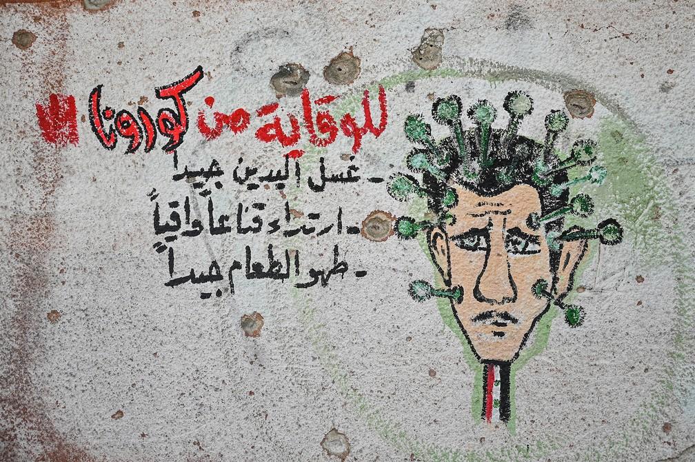 Grafite representando o presidente sírio Bashar al-Assad como o coronavírus é visto na parede de uma escola destruída em Binnish, bairro de Idlib, perto da fronteira com a Turquia. Foto de 10 de março — Foto: Ozan Kose/AFP