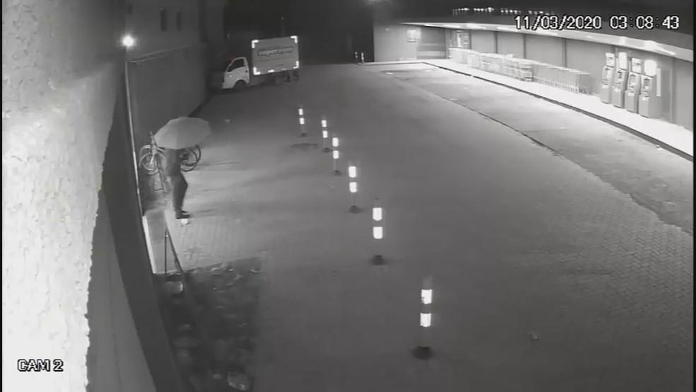 Assaltante usa sombrinha para se esconder das câmeras de segurança durante tentativa de assalto em supermercado  — Foto: PCDF/Divulgação