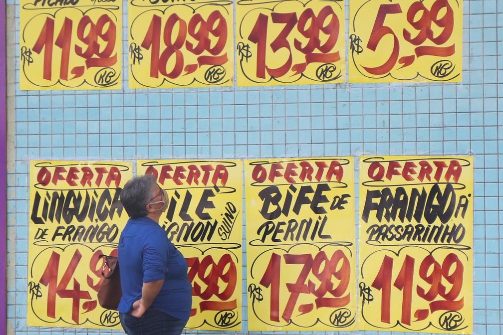 Mulher observa cartazes com preços em açougue em São Paulo, em imagem de julho. — Foto: LUCIANO CLAUDINO/CÓDIGO19/ESTADÃO CONTEÚDO