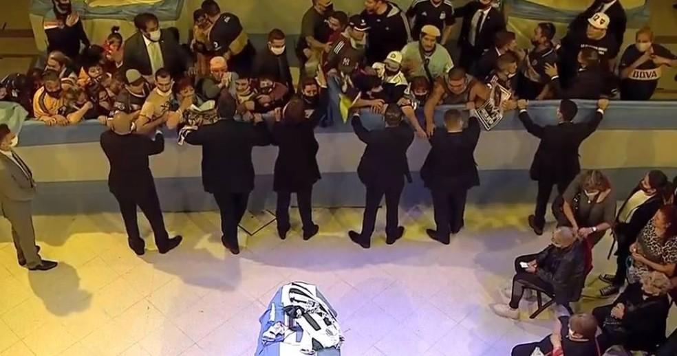 Torcedores jogam flores e camisas sob o caixão de Maradona, coberto com camisas da Argentina e do Boca Juniors - Foto: Reprodução / GloboNews