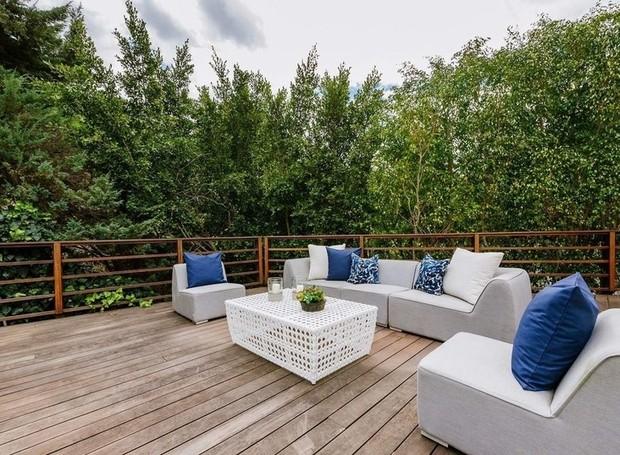 Um deck de madeira é cercado por arbustos que criam uma área de relaxamento com privacidade (Foto: Homes.com)