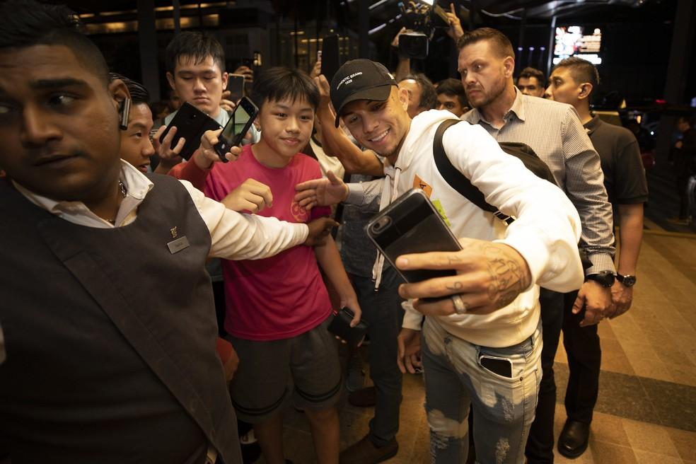 Everton Cebolinha tira foto com fã na chegada ao hotel da seleção brasileira na Malásia — Foto: Lucas Figueiredo/CBF