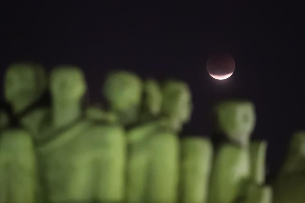 Lua cheia vista à partir do Monumento às Bandeiras, no Parque do Ibirapuera, zona sul de São Paulo, durante o mais longo eclipse lunar do século 21, nesta sexta-feira, 27.  (Foto: Alex Silva/Estadão Conteúdo)