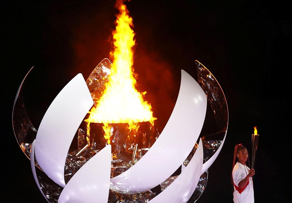 Naomi Osaka segura a tocha olímpica após acender a pira olímpica durante a cerimônia de abertura dos Jogos Olímpicos de Tóquio, no Japão — Foto: Mike Blake/Reuters