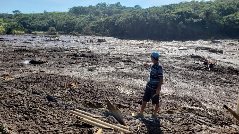 'Seu' Abel mostra onde ficava a casa dele; ao fundo três homens da equipe de busca fazem uma varredura por vítimas — Foto: Raquel Freitas/G1