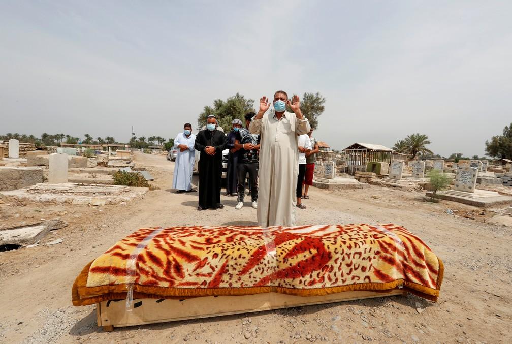 Homens se reúnem, neste domingo (25), em funeral de vítima de incêndio em um hospital de Bagdá, no Iraque, no dia 24. Dezenas de pessoas morreram. — Foto: Thaier Al-Sudani/Reuters