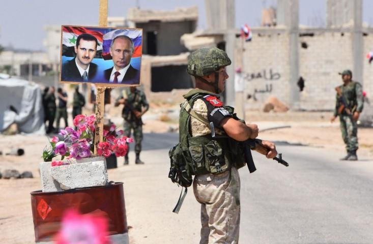 Soldados perto de imagens dos presidente da Síria, Bashar al-Assad, e da Rússia, Vladimir Putin