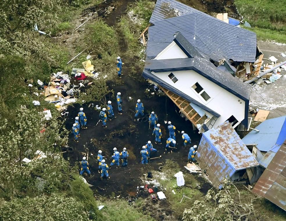 -  Policiais procuram sobreviventes de uma casa danificada por um deslizamento de terra causado por um terremoto na cidade de Atsuma, Hokkaido, norte do