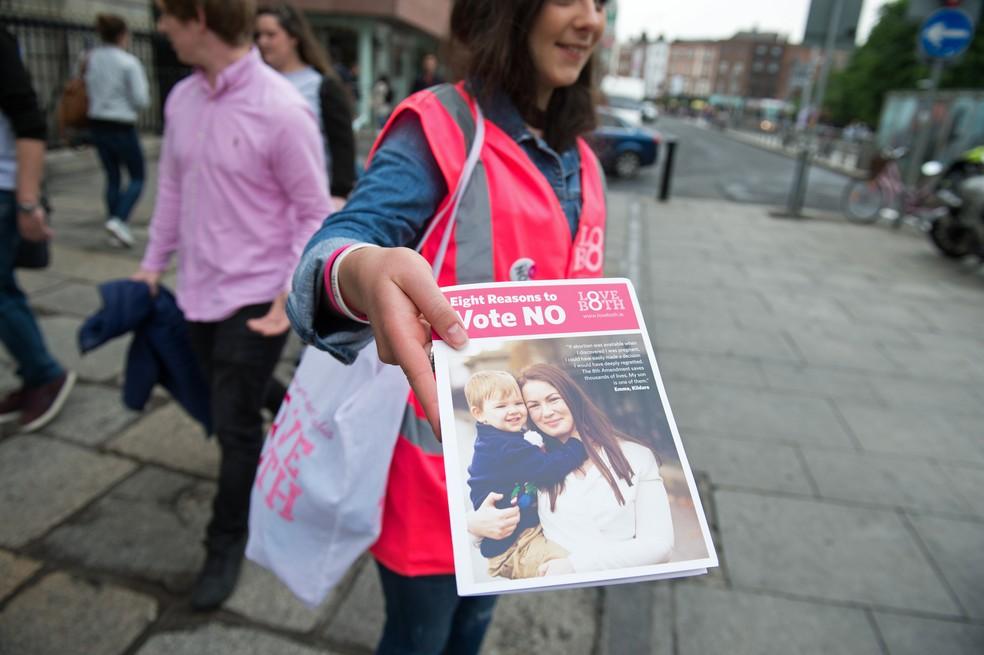 Mulher distribui folheto em campanha contra o fim da proibição do aborto (Foto: Barry Cronin/AFP )