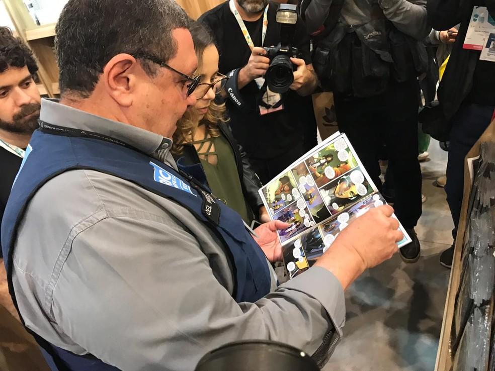 Subsecretário de Ordem Pública folheia livro na Bienal em busca de conteúdo 'impróprio' — Foto: Fernanda Rouvenat / G1