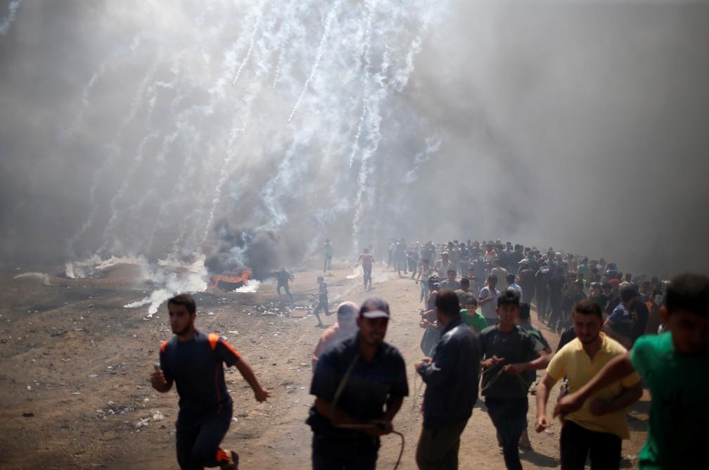 Manifestantes palestinos correm para se proteger de bombas de gás atiradas por tropas israelenses durante protesto na fronteira de Israel com Gaza contra a inauguração de embaixada dos EUA em Jerusalém (Foto: Mohammed Salem/Reuters)