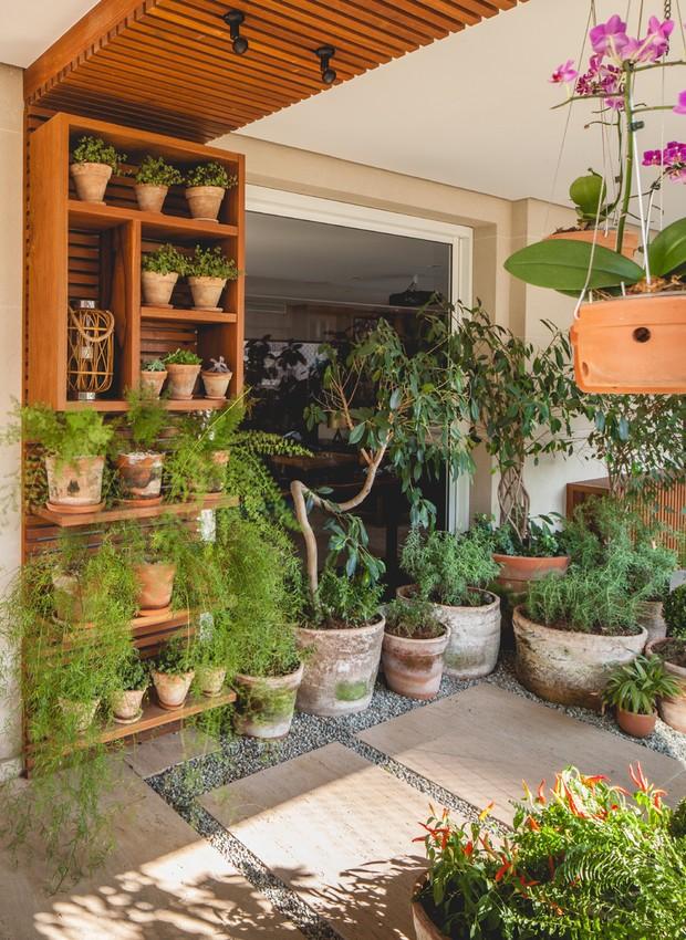 Uma estante de madeira oculta a fiação elétrica e comporta pequenos vasos e objetos decorativos  (Foto: Gui Gomes/Divulgação )