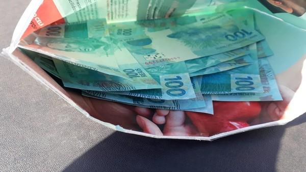 Notas falsas de R$ 100 estavam em um folheto — Foto: Polícia Militar