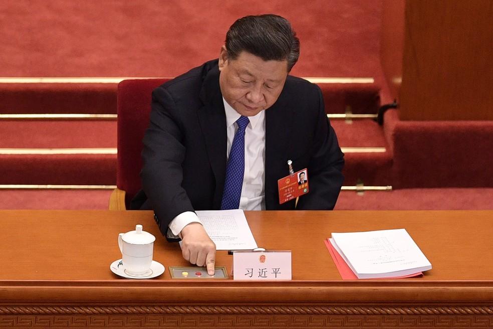 Presidente chinês, Xi Jinping, vota em uma proposta para elaborar uma lei de segurança em Hong Kong durante a sessão de encerramento do Congresso Nacional do Povo, em Pequim, em 28 de maio. O parlamento da China aprovou o projeto da lei de segurança nacional a Hong Kong — Foto: Nicolas Asfouri / AFP