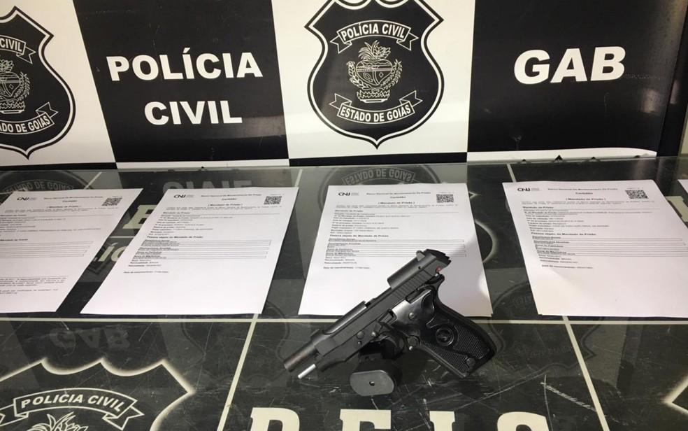 Pistola apreendida na operação e mandados de prisão expedidos contra suspeitos — Foto: Lis Lopes/G1