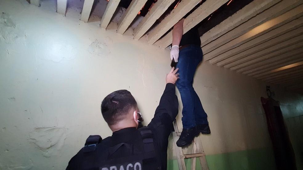 Agente localizou aparelho celular no forro de um dos pavilhões — Foto: Polícia Civil/Divulgação