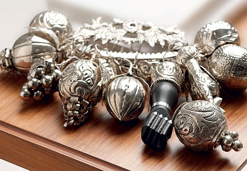 Amuleto de origem africana, a penca de balangandãs virou objeto de decoração. O enfeite reúne peças de simbolismo de orixás do candomblé. Reza a crença que afasta mau-olhado e forças negativas. Modelos como este podem ser encontrados no Mercado Modelo