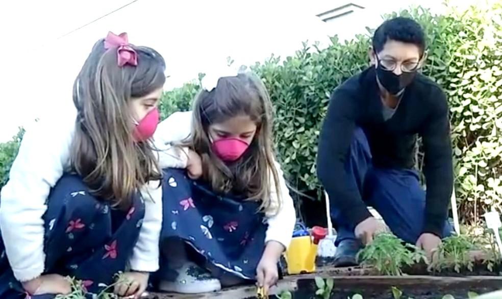 Jardineiro Arnaldo José Rodrigues divide com as crianças seus conhecimentos no cultivo de plantas — Foto: TV TEM/Reprodução