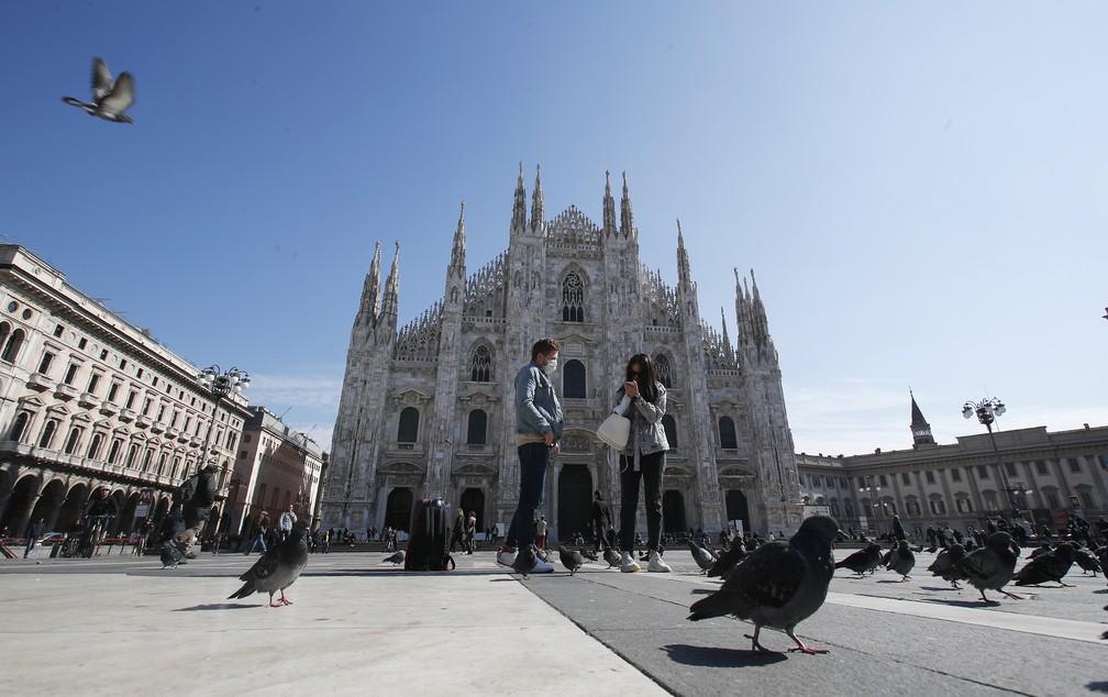Pedestres usam máscaras em frente à Piazza del Duomo, em Milão, uma das regiões mais afetadas pela epidemia de coronavírus na Itália — Foto: AP Photo/Antonio Calanni