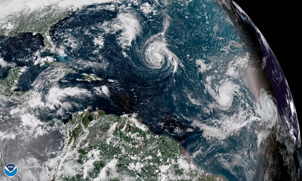 -  Imagem de satélite mostra os furações Florence  3º da dir. p/ esq.  e Helene  à dir. , além da tempestade tropical Isaac  centro , no Oceano Atlântic