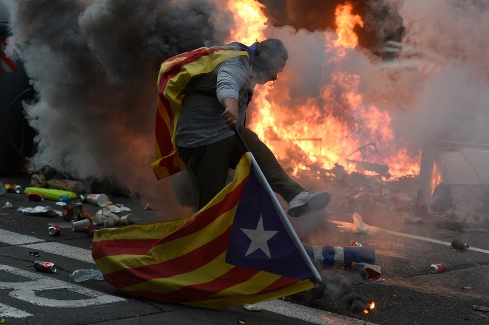 Manifestante independentista carrega bandeira catalã em meio a protesto em Barcelona, nesta sexta-feira (18) — Foto: AFP/Josep Lago