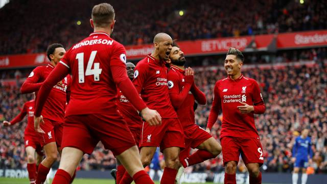 Calah comemora gol do Liverpool em pose de meditação, abraçado por Fabinho e observado por Roberto Firmino