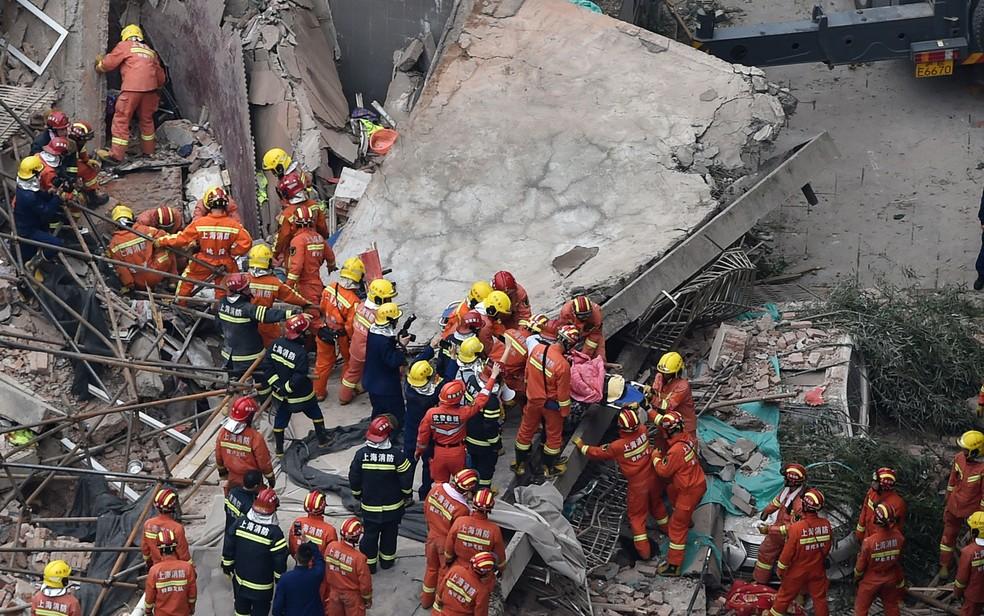 Equipes de resgate trabalham no local de escombros após desabamento de imóvel em Xangai — Foto: Hector Retamal / AFP Photo