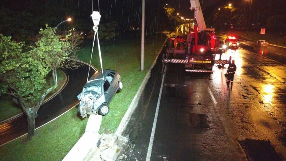 Guindaste iça e retira carro que havia ficado pendurado em mureta de proteção de viaduto no DF após acidente (Foto: Corpo de Bombeiros/Divulgação)