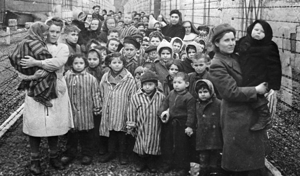 Médicos soviéticos e representantes da Cruz Vermelha são vistos entre prisioneiros do campo de concentração de Auschwitz pouco antes da libertação em 27 de janeiro de 1945 — Foto: Sputnik via AFP