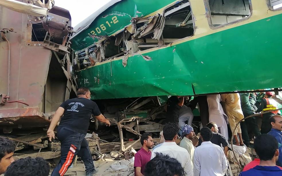 Socorristas paquistaneses e moradores se reúnem em volta dos destroços de trens que se chocaram no Paquistão — Foto: STR / AFP Photo