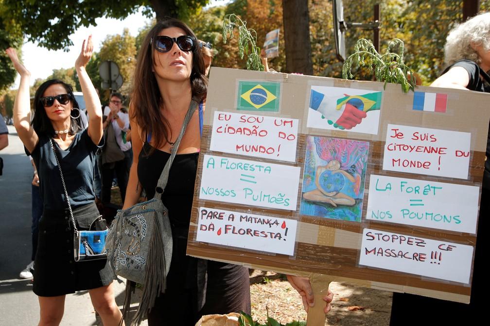 Manifestante leva cartazes para pedir a preservação da Amazônia em protestos em frente à embaixada brasileira em Paris nesta sexta-feira (23). — Foto: Charles Platiau/Reuters