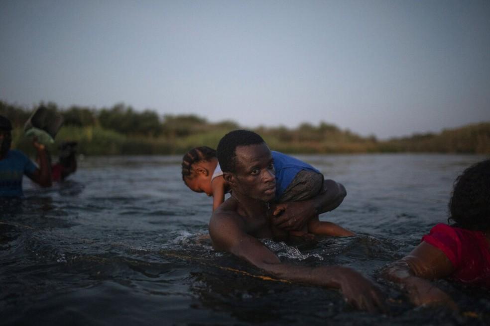 Imigrante atravessa o Rio Grande para chegar aos EUA com uma criança no ombro, em 20 de setembro de 2021 — Foto: Felix Marquez/AP