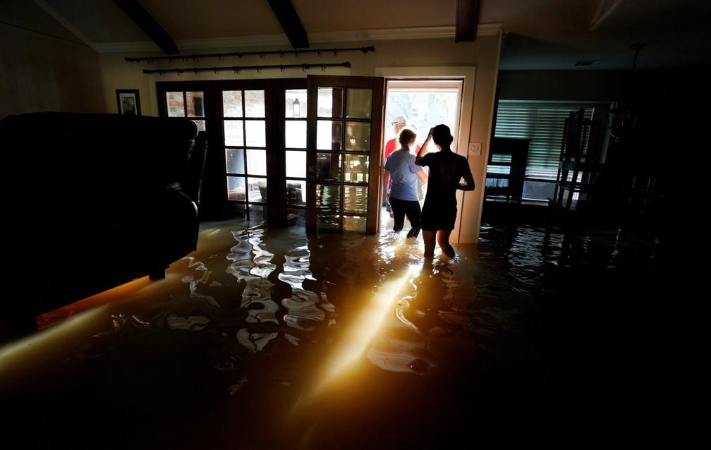 Família retira seus pertences de casa alagada após a passagem do furacão Harvey em Houston, nos EUA. Foto tirada na quinta (31) e divulgada nesta sexta (1º) (Foto: Rick Wilking/Reuters)