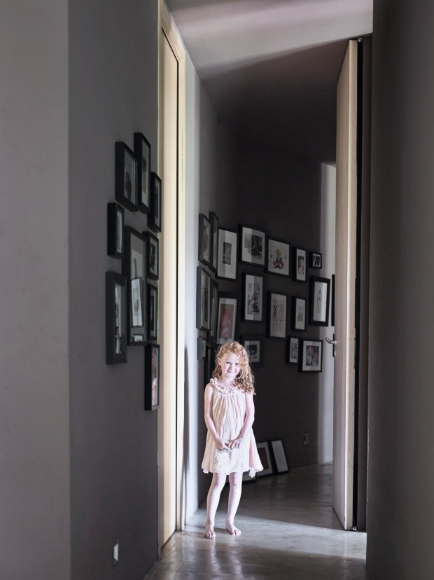 Corredor. Paredes e teto foram pintados com o mesmo tom de cinza-escuro. Em molduras pretas compradas na Ikea, os desenhos feitos pelos filhos e as fotos de família enfeitam o espaço. Na foto, Giulia, a sobrinha da moradora (Foto: Fabrizio Ciccone / Living Inside)
