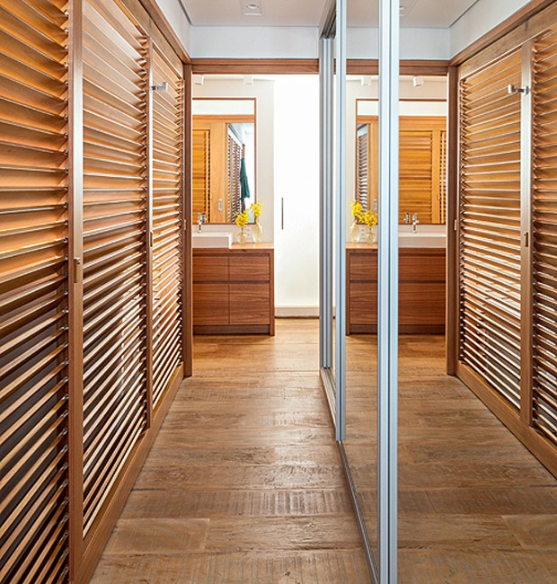 Os painéis de freijó dividem o ambiente – quarto de um lado, closet do outro. Os armários com espelhos nas portas ampliam o espaço. Projeto do escritório de arquitetura Archeufficio (Foto: Lufe Gomes/Editora Globo)