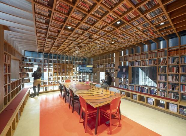 Uma sala de leitura é decorada por uma paleta quente, de tons de vermelho, laranja e madeira. Detalhe: no teto, ripas formam um quadriculado, imitando nichos que guardam livros (Foto: Ossip Architectuurfotografie/ Arch Daily/ Reprodução)