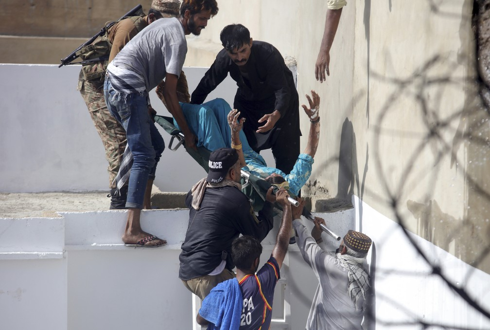 Voluntários carregam homem ferido após queda de avião comercial em área residencial perto do aeroporto de Karachi, no Paquistão — Foto: Fareed Khan/AP