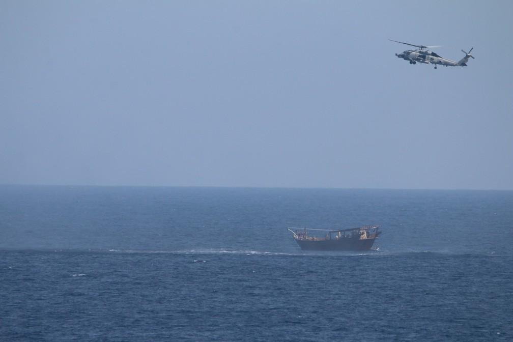 Helicóptero SH-60 Seahawk, designado pelo cruzador de mísseis guiados USS Monterey, voa acima de embarcação que levava carregamento de armas ilícitas em águas internacionais do Mar da Arábia do Norte. Foto tirada em 6 de maio de 2021. — Foto: Marinha dos EUA via Reuters