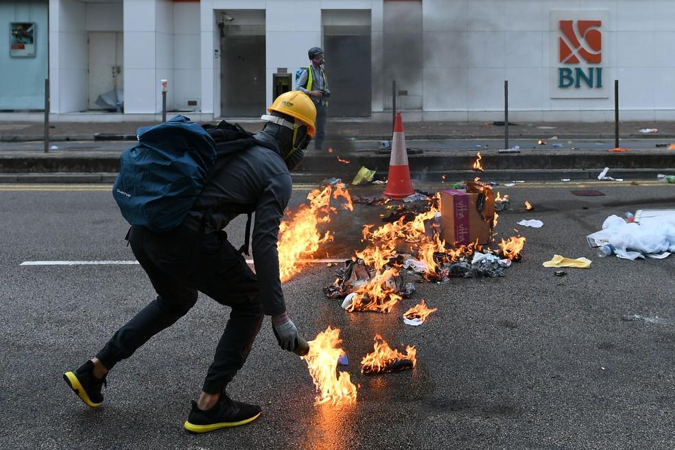 Manifestante coloca fogo em destroços na rua durante manifestação em Hong Kong, nesta terça-feira (1º)  — Foto: Mohd Rasfan / AFP