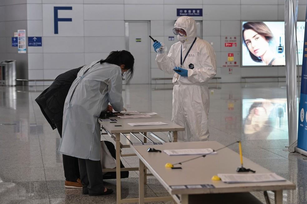 Funcionário do Aeroporto Internacional Pudong de Xangai usa equipamento de proteção em meio às preocupações com o coronavírus nesta quarta-feira (18)  — Foto: Hector Retamal / AFP