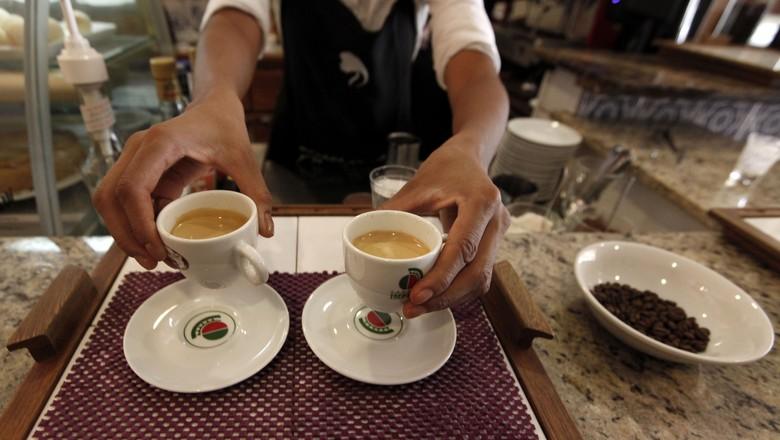 Garçom serve clientes em uma cafeteria em São Paulo; consumo da bebida tem se firme pelo mundo apesar da pandemia (Foto: REUTERS/Nacho Doce)