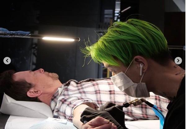 O ator Michael J. Fox deitado enquanto era feita a tatuagem em seu braço (Foto: Instagram)