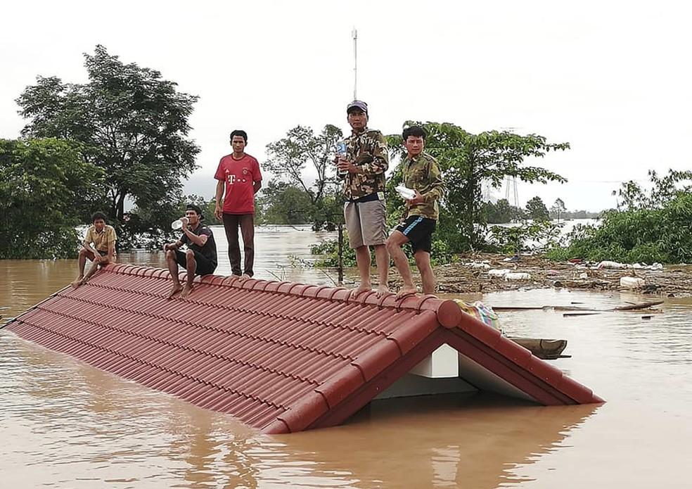 Moradores se protegem nesta terça-feira (24) em telhado de casa de inundação na província de Attapeu, no Laos (Foto: Attapeu Today via AP)