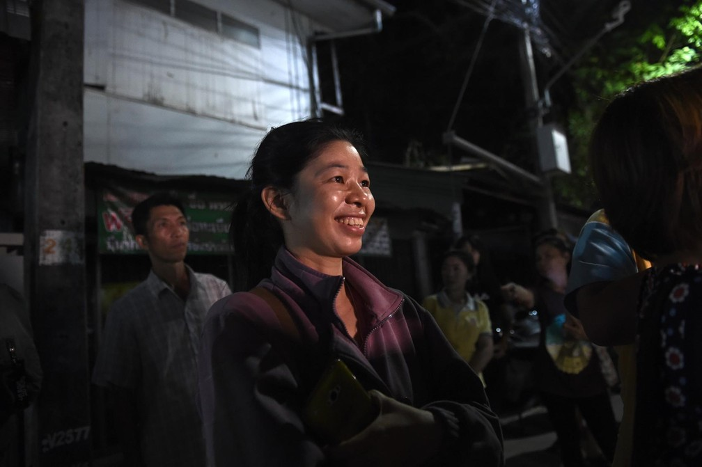Moradora sorri próximo ao hospital em que as crianças estão internadas em Chiaang Rai, na Tailândia, nesta terça-feira (10) (Foto: Lillian Suwanrumpha/AFP)