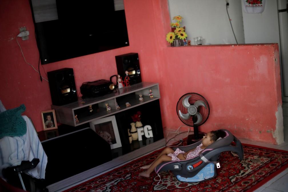 """Maria Giovanna """"Gigi"""" da Silva, que tem dois anos e nasceu com microcefalia, sentada na casa em que mora, no Recife — Foto: Ueslei Marcelino/Reuters"""